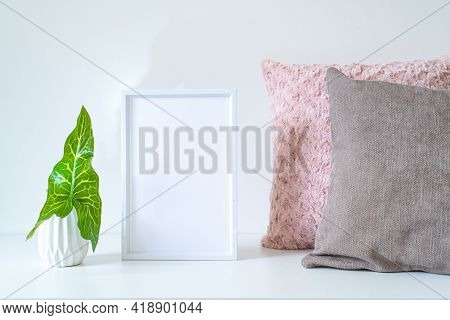 Empty White Frame Mockup On White Table. Soft Colored Cushions And White Vase With An Arum Italicum