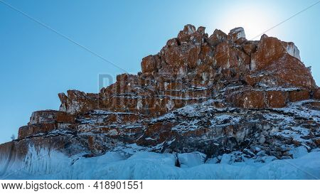 A Picturesque Rock, Devoid Of Vegetation, Against The Backdrop Of A Blue Sky. Snow Lies On The Reddi