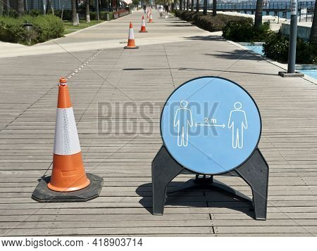 Social Distancing Signboard And Traffic Cones With Barricade Tape During Coronavirus Pandemic