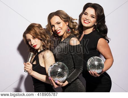 Three charming ladies dressed in black cocktail dresses singing with a microphone, holding disco balls and smiling.