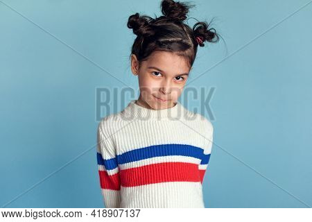 Serious Little Girl With Funny Hairstyle, Stading Over Studio Blue Background. Kid Has A Shy Express