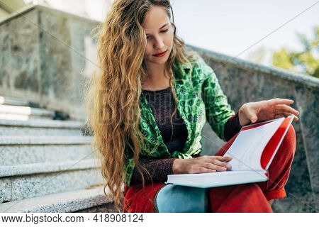 Pretty Student Female Reading A Book While Sitting On The Stairs Of The College Campus On A Sunny Da