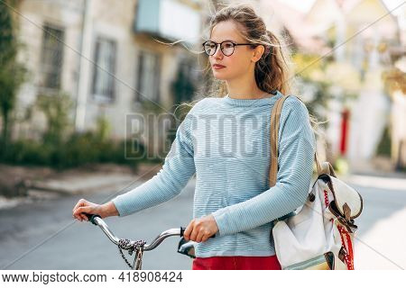 Pretty Student Female Going To The University With A Bike On A Sunny Day Outdoors. Pretty Woman In C