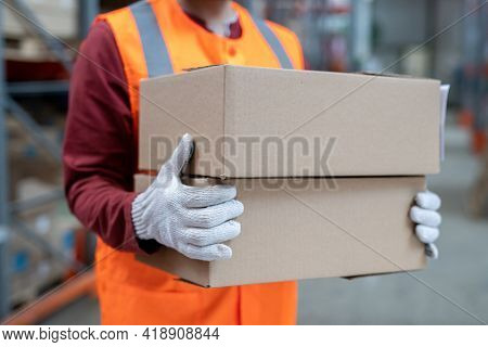 Close-up of unrecognizable warehouse worker carrying boxes while sorting it at stockroom