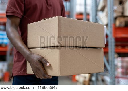 Close-up of unrecognizable Black mover carrying two cardboard boxes along stockroom