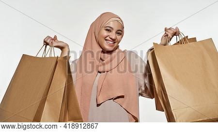 Portrait Of Happy Young Arabian Girl In Traditional Hijab Holding Shopping Packets And Smiling At Ca