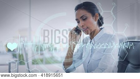 Digital medical symbols and heartbeat graphic over mixed race businesswoman talking on smartphone. global technology, data processing and digital interface concept digitally generated image.