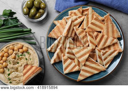 Delicious Pita Chips With Creamy Hummus Served On Grey Table, Flat Lay