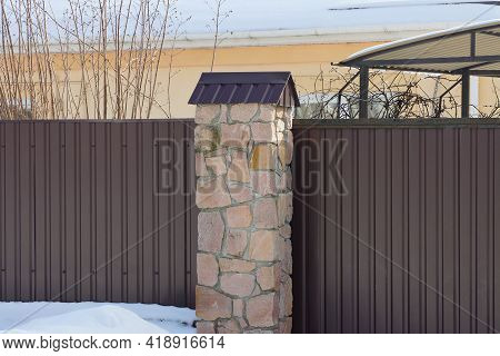 Part Of A Brown Wall Of A Fence Made Of Stones And Metal In White Snow On A Winter Street