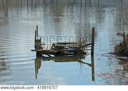 One Old Broken Gray Wooden Footbridge Over Lake Water Near The Shore