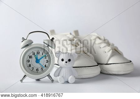 Alarm Clock, Toy Bear And Baby Booties On White Background. Time To Give Birth