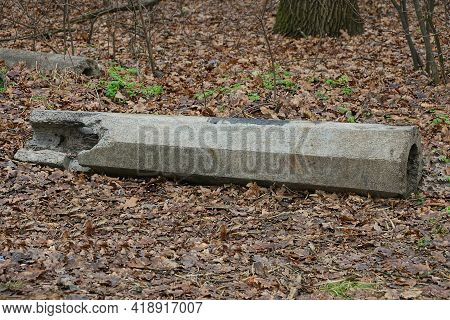 One Piece Of Old Gray Concrete Pillar Lies In Brown Fallen Leaves Outside