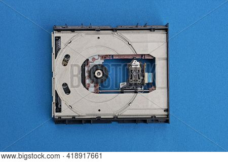 Part Of Old Electronic Optical Drive With Laser On Blue Table
