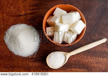 There Is Lump Sugar In A Clay Bowl, White Granulated Sugar In A Wooden Spoon And On A Kitchen Board.