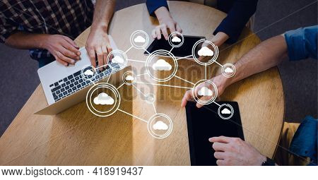 Connected network of bubbles with cloud icons over businessmen at table with laptop and tablets. global technology, data processing and digital interface concept digitally generated image.