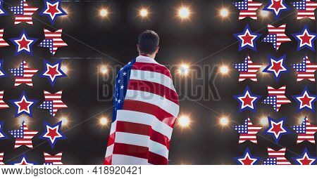 Composition of american flag stars and man wrapped in american flag over sports stadium spotlights. american patriotism and sport concept digitally generated video.