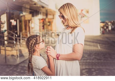Outdoor Portrait Of Beautiful Blonde Mother And Her Cute Child. Small Girl Hugging Her Mom On The Be