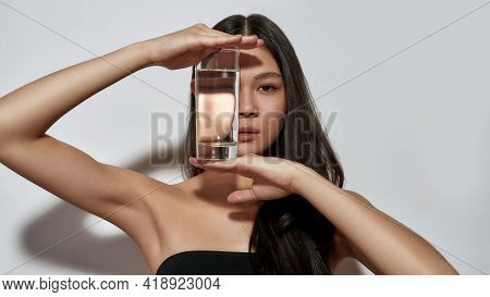 Cute Young Asian Girl Hiding Face Behind Water In Glass While Posing On Light Background And Looking