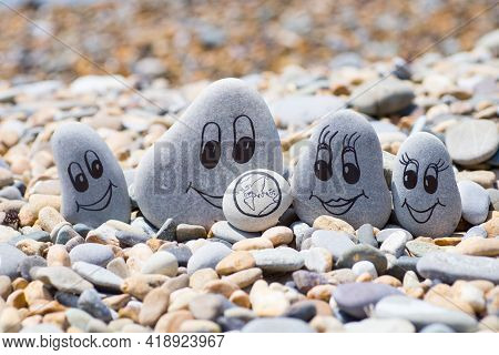 Pebbles With Drawn Faces In The Sand. Father, Mother, Daughter And Son. Family Vocation Concept.