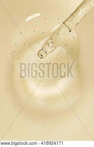 Liquid Serum And Dropper On A Beige Background Top View. Serum Drops In The Form Of A Circle With A