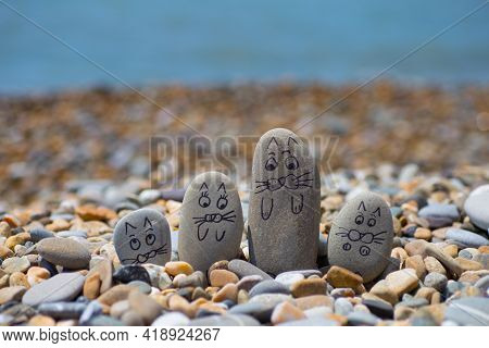 Pebbles With Drawn Faces In The Sand. Father, Mother, Daughter And Son. Family Of Cats Vocation Conc