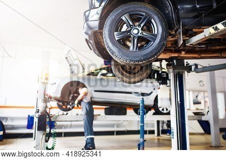 The Car Is Lifted For Repair On A Lift In A Car Service Station, A Mechanic In Overalls Repairs In T