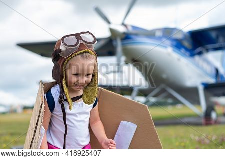 A Cute Little Girl Dressed In A Cap And Glasses Of A Pilot On The Background Of An Airplane. The Chi
