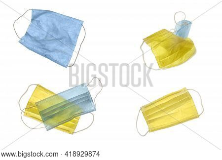 A Combination Of Blue And Yellow Covid Face Masks, Isolated On White.