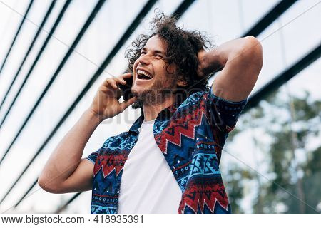 Joyful Young Man With Curly Hair Smiling Broadly While Talking With His Friend On Mobile Phone Outdo