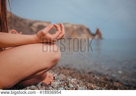 Young Woman In Red Swimsuit With Long Hair Practicing Stretching Outdoors On Yoga Mat By The Sea On