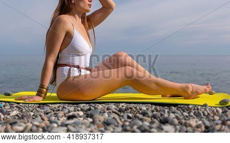 Young Woman In White Swimsuit With Long Hair Practicing Stretchi