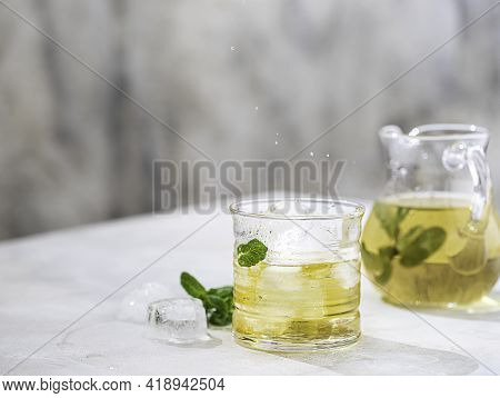 Summer Iced Green Tea With Fresh Mint On Light Table. Food In Motion Concept. Summer Cold Drink Cock