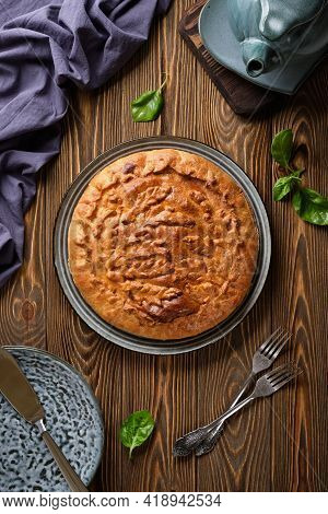 Delicious Pie With Meat And Potatoes With A Crispy Crust On A Blue Plate On A Wooden Table