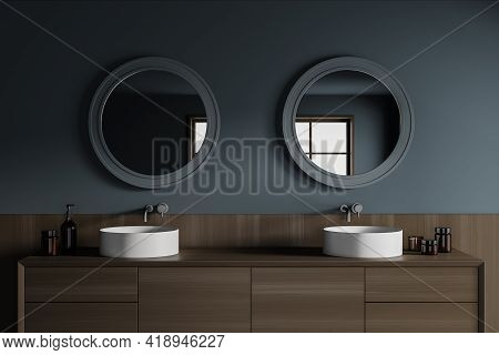 Dark Stylish Bathroom Interior With Two Separate Sinks And Wooden Drawer With Bottles Of Gel, Two Ro