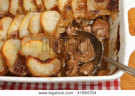 Lancashire hotpot with lamb, kidney and potatoes in casserole dish.