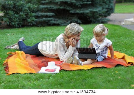 early learning - white woman, mother  watching her daughter using  tablet.outdoor scene.