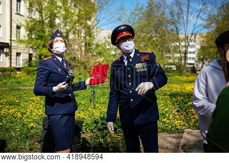 A Little Girl In A Military Uniform And A Medical Mask On Her Face. A Solemn Costumed Procession On