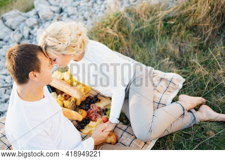 Barefoot Woman Leaned Her Forehead Against Man Sitting On A Blanket. Man And Woman Are Holding Hands