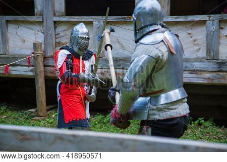 Two Militant Medieval Knights Fighting At Historical Festival. Fantasy, Reenactment And Medieval Cul