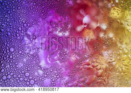 Multi-colored Drops Of Oil On The Water. Circles Of Rainbow Color Or Spectrum. Abstract Bright Backg