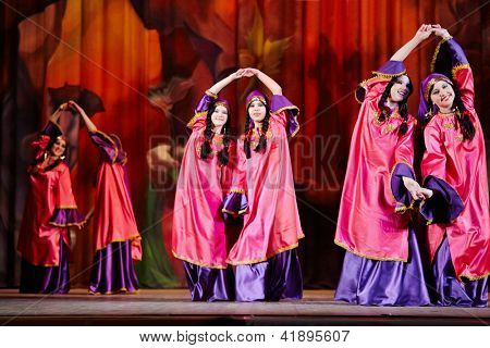 MOSCOW - JAN 28: Teenage dancing collective dressed in oriental dress dances on stage of Red October Culture Palace during Bellydance Superiority of Moscow, Jan 28, 2012, Moscow, Russia.