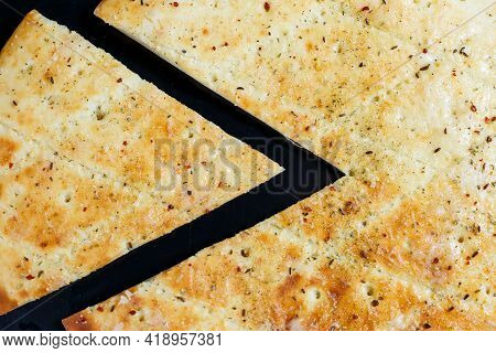 Sliced Pizza On A Black Stone Background, Top View. Freshly Baked Focaccia With Cheese