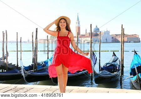 Happy Young Woman In Red Dress Walking In Venice, Italy. Smiling Girl Posing In Venice, Italy.