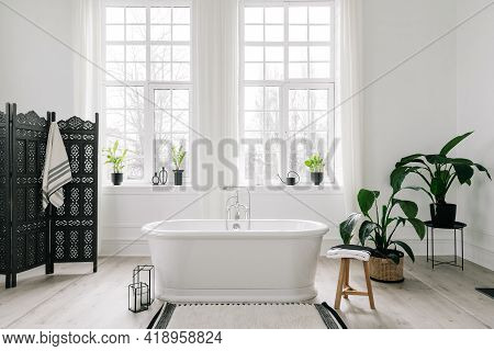 Home Decor Ideas In Contemporary Bathroom Design. Empty Freestanding Bathtub Against Large Windows,
