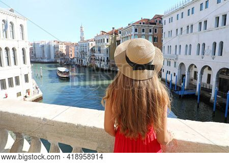 Holidays In Venice. Back View Of Beautiful Girl In Red Dress Enjoying View Of Grand Canal From Rialt