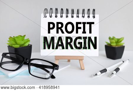 Profit Margin. Text On White Paper, Notebook On A Stand On A Light Background Near Glasses And Plant