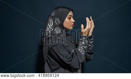 Profile Of Young Arabian Woman In Hijab Looking At Her Palms While Posing Sideways On Dark Blue Back