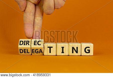 Directing Or Delegating Leadership Style Symbol. Businessman Turns Cubes, Changes Words 'delegating'