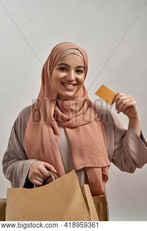 Happy Young Arabian Woman In Hijab With Bags And Paying Card Smiling At Camera On Light Background,