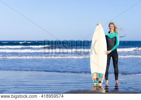 Blonde Caucasian Woman With A Surfboard On Beach. Smiling And Posing With Surf Board Near Blue Ocean